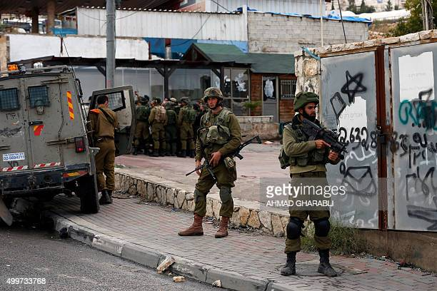 TOPSHOT Israeli security forces stand at the site of an attack in the West Bank village of Hizma north of Jerusalem in which an Israeli soldier was...