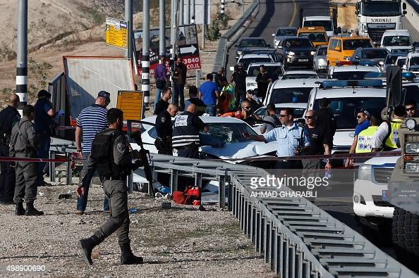 Israeli security forces stand at the site where a Palestinian man rammed his car into Israelis soldiers standing by a bus station on a highway next...