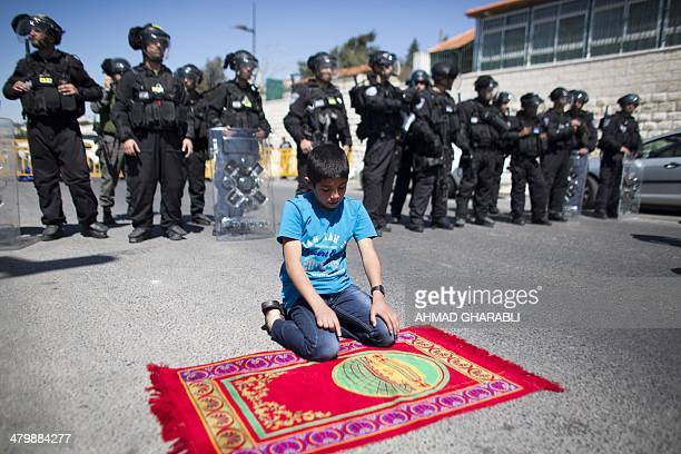 Israeli security forces stand guard as a Palestinian boy performs Friday prayers outside Jerusalem's Old City on March 21 2014 after Israeli police...