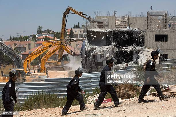 Israeli security forces stand guard as bulldozers under an Israeli High Court ruling start the demolition of the socalled Dreinoff buildings in the...