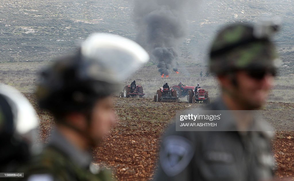 Israeli security forces stand guard as Jewish settlers from the Esh Kodesh settlement stage a sit-in in an attempt to prevent Palestinians from working in their fields in the northern West Bank village of Jalod on January 2, 2013. AFP PHOTO/JAAFAR ASHTIYEHs