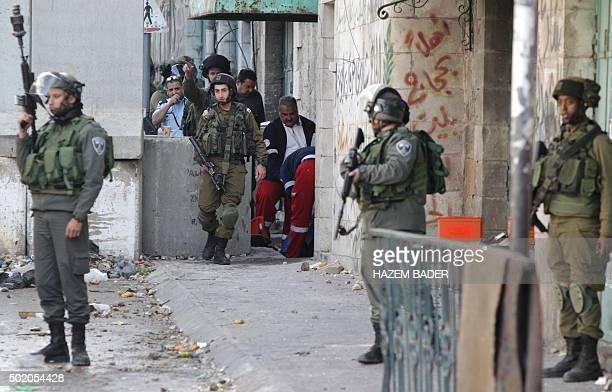 Israeli security forces stand guard as members of the Palestinian Red Crescent give medical aid to a Palestinian woman who attempted to stab Israeli...