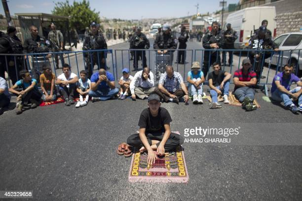 Israeli security forces stand guard as Palestinian Muslim worshipers perform traditional Friday prayers in a street outside the Old City in East...