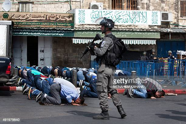 Israeli security forces stand guard as Palestinian Muslim worshipers pray on a street outside Jerusalem's Old City following restrictions by Israeli...