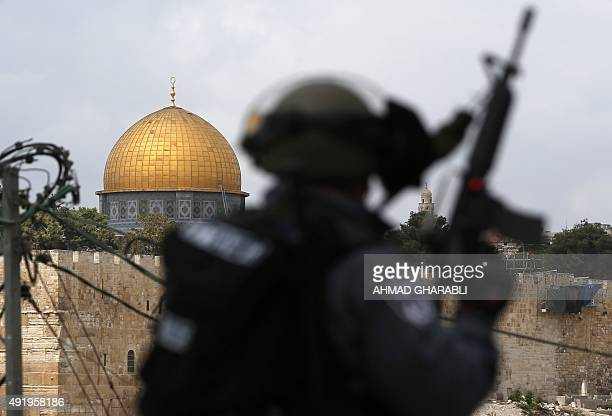 Israeli security forces stand guard as Palestinian Muslim worshippers take part in Friday noon prayers in the east Jerusalem neighborhood of Ras...