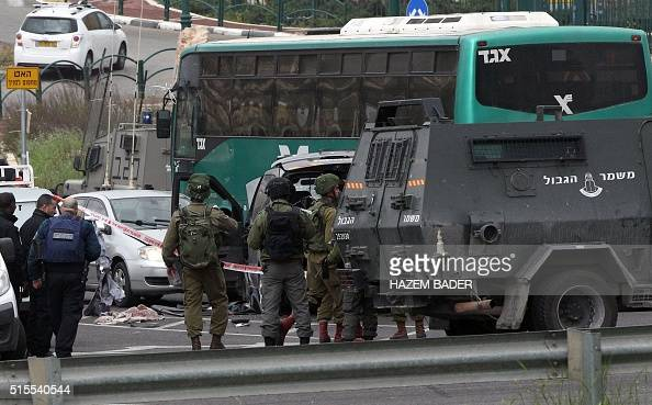 Israeli security forces stand guard at the scene where three Palestinians carried out two attacks a shooting and a car ramming on Israelis at a bus...