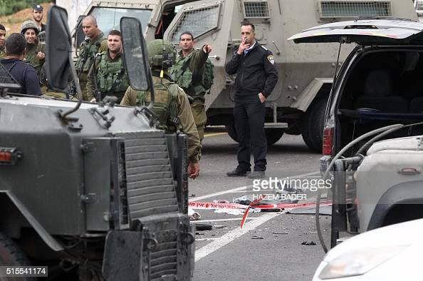 Israeli security forces stand guard at the scene where three Palestinians carried out two attacks a shooting and a car ramming on Israelis at the...