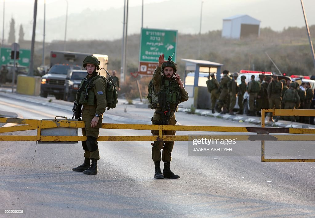 Israeli security forces stand guard at the site of a car ramming attack at the Huwara checkpoint near the West Bank city of Nablus on December 26...