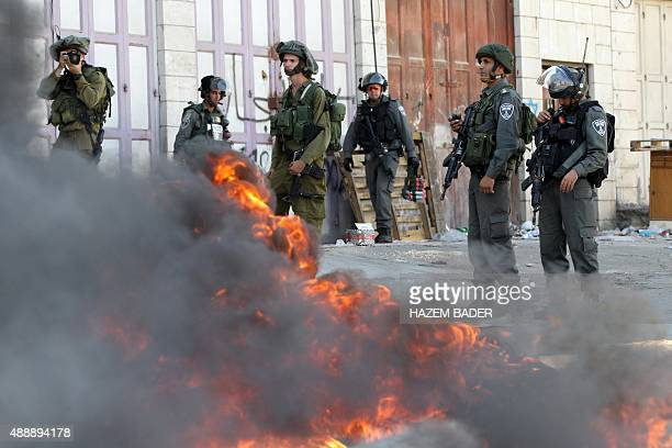 Israeli security forces stand guard behind burning tires during clashes with Palestinian protesters following an antiIsraeli protest after the weekly...