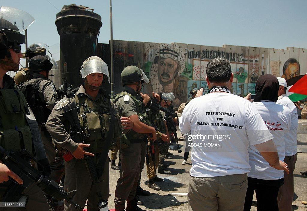 Israeli security forces stand guard facing protesters during a rallye in support of Palestinian journalists who call for freedom of movement on July 17, 2013 at the Qalandia checkpoint between Ramallah and Jerusalem, in the occupied West Bank.