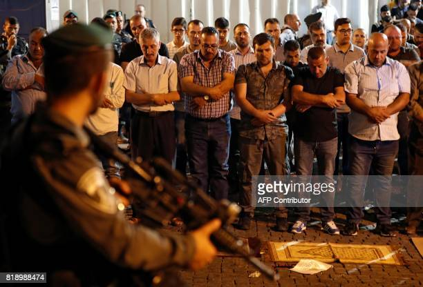 TOPSHOT Israeli security forces stand guard in front of Palestinian Muslim worshippers praying outside Lions Gate a main entrance to the AlAqsa...