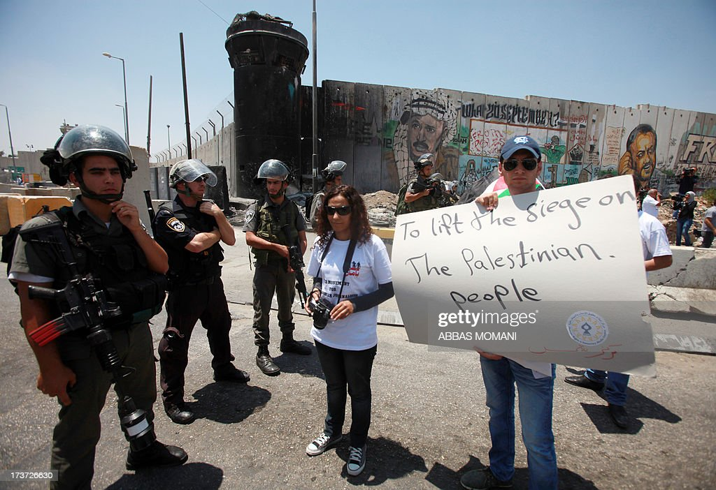 Israeli security forces stand guard near Palestinian journalists who demonstrate claiming for freedom of movement on July 17, 2013 at the Qalandia checkpoint between Ramallah and Jerusalem, in the occupied West Bank. Theplacard reads in English: ' to lift the siege on the Palestinian people'.