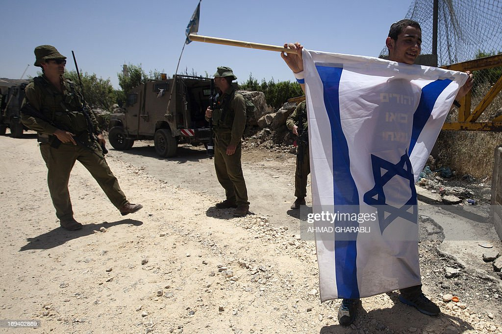 Israeli security forces stand guard next to a Jewish settler waving an Israeli flag as protesters from the settlements of Gush Etzion and Kiryat Arba gather on Route 60, mainly used by settlers, near the Palestinian village of Al-Khader in the occupied West Bank on May 24, 2013 to protest against recent stonethrowing and firebomb attacks in the area.