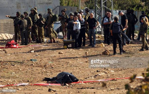 Israeli security forces stand near the body of Palestinian man who was killed after he tried to stab an Israeli soldier in the village of Sair north...