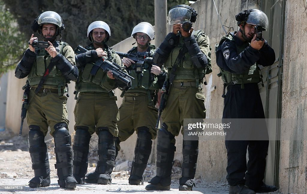 Israeli security forces stand with their weapons monitoring the situation during clashes with Palestinian protester following a demonstration against...