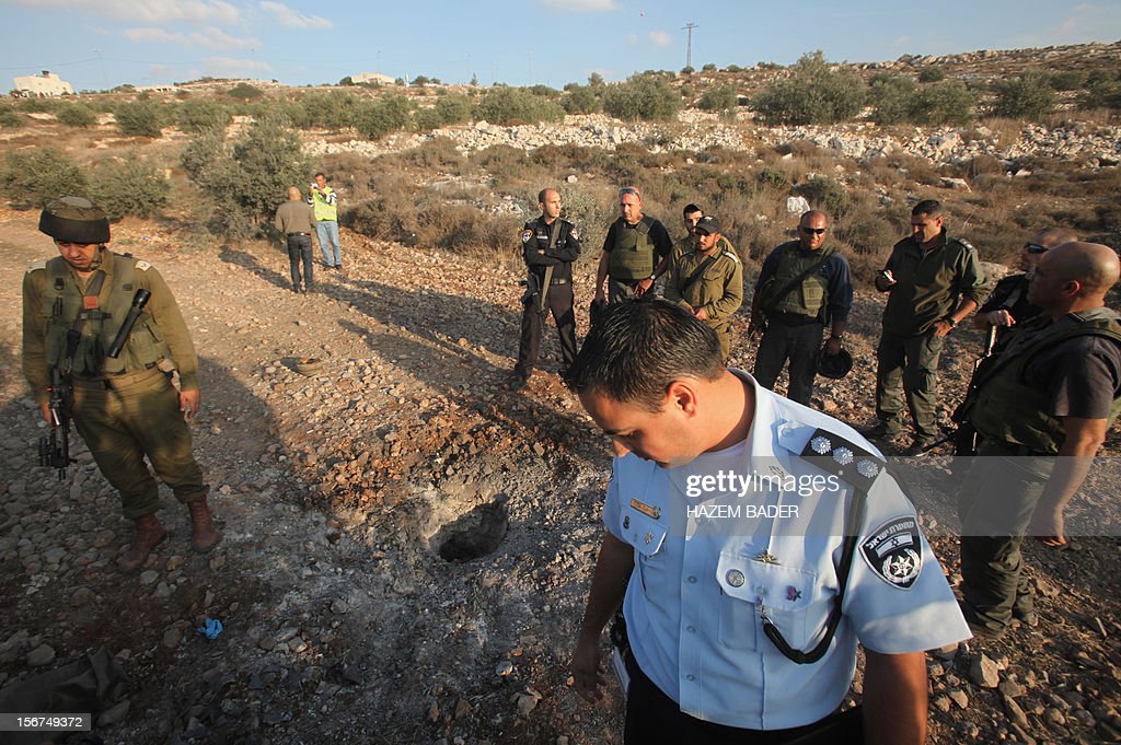 Israeli security forces surround the place where a rocket fired by Palestinian militants from the Gaza Strip landed in an olive grove in West Bank near Jerusalem on November 20, 2012. The rocket from Gaza struck an olive grove in West Bank near Jerusalem, shortly before UN chief Ban Ki-moon arrived for talks on ending the Gaza crisis. The attack was claimed by the armed wing of Gaza's ruling Hamas movement, in the second such attempt to target Jerusalem in four days. BADER