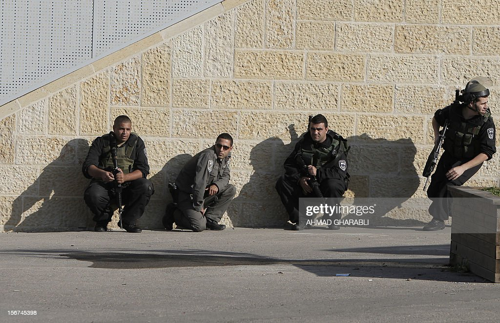 Israeli security forces take cover as air raid sirens sound around Jerusalem on November 20, 2012. A rocket struck just south of Jerusalem as UN chief Ban Ki-moon was to arrive for talks on ending the Gaza crisis, AFP correspondents said. AFP PHOTO/AHMAD GHARABLI