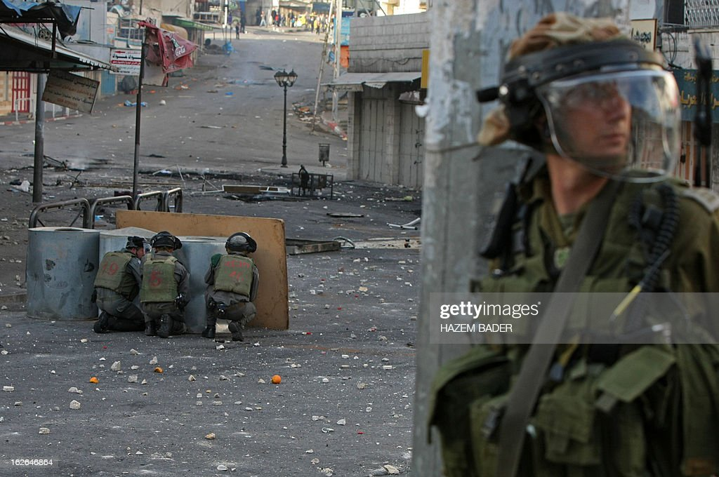 Israeli security forces take cover behind barrels during clashes with Palestinian protestors near the Israeli checkpoint in the West Bank town of Hebron on February 25, 2013, following the funeral of a Palestinian man who died in an Israeli prison. Thousands of angry mourners attended the West Bank funeral of Arafat Jaradat who the Palestinians say was tortured to death in an Israeli jail, as masked militants vowed to take revenge.