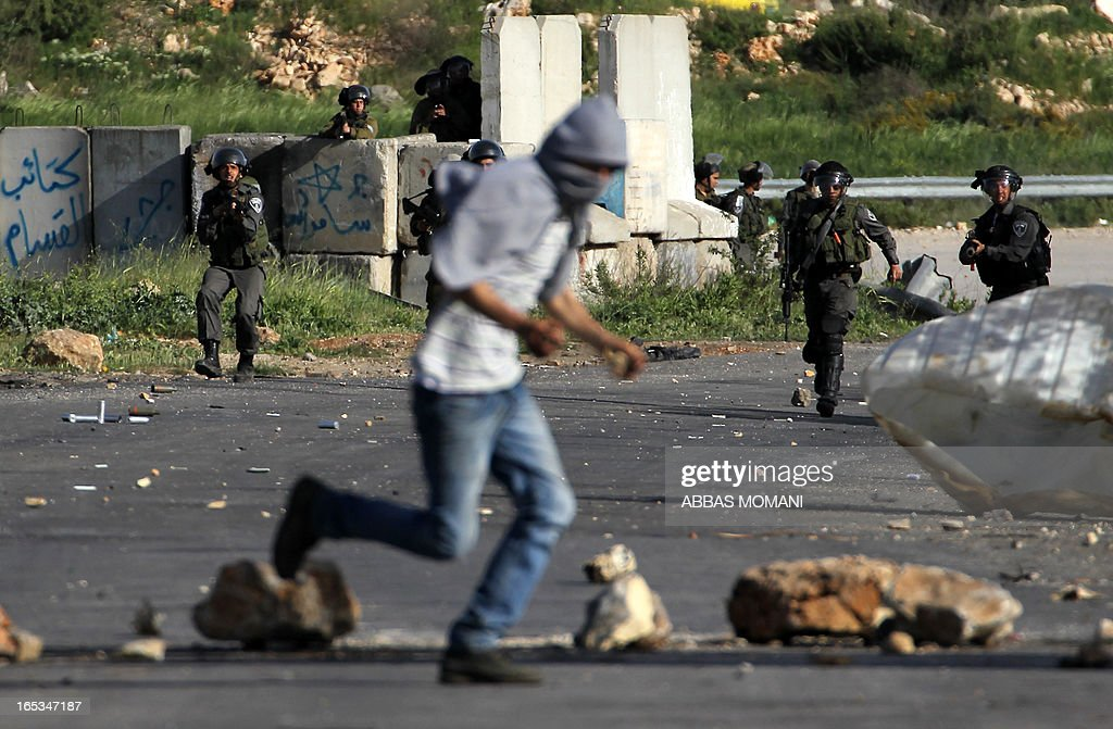 Israeli security forces take position as a Palestinian protester runs for cover during clashes outside Ofer prison near the West Bank city of Ramallah on April 3, 2013 following a protest against the death of a Palestinian prisoner while in detention. Maisara Abu Hamdiyeh, who had served 10 years of a life sentence for attempted murder, died in an Israeli hospital two months after being diagnosed with throat cancer. The Palestinian leadership has accused Israel of medical negligence with news of his death sparking angry clashes. AFP PHOTO/ ABBAS MOMANI