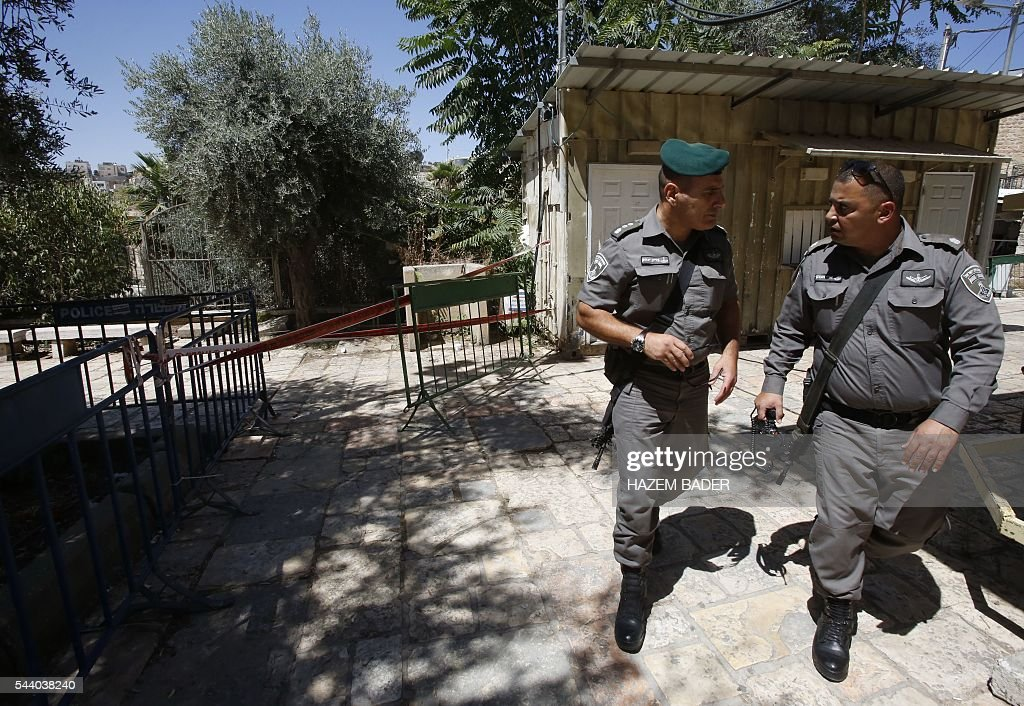 Israeli security forces walk on July 1, 2016 near an Israeli security barrier in the flashpoint city of Hebron, in the occupied West Bank, after a Palestinian woman attempted to stab an Israeli guard and was shot dead, according to Israeli police. Israeli authorities said that no police were wounded in the attempt at the site in the southern West Bank city of Hebron, near a religious site known to Muslims as the Ibrahimi Mosque and to Jews as the Cave of the Patriarchs. BADER