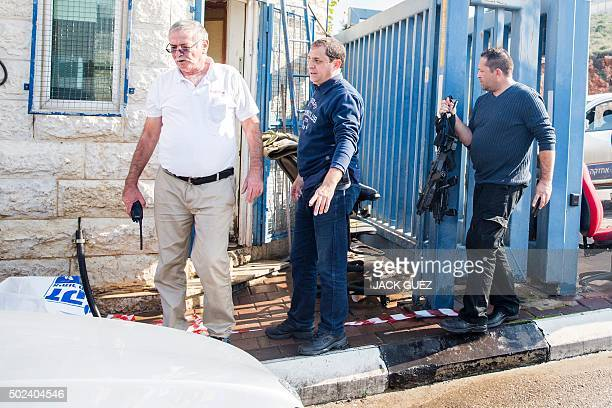 Israeli security guards inspect a car near the scene where a Palestinian assailant was shot dead after he stabbed two Israeli security guards at an...