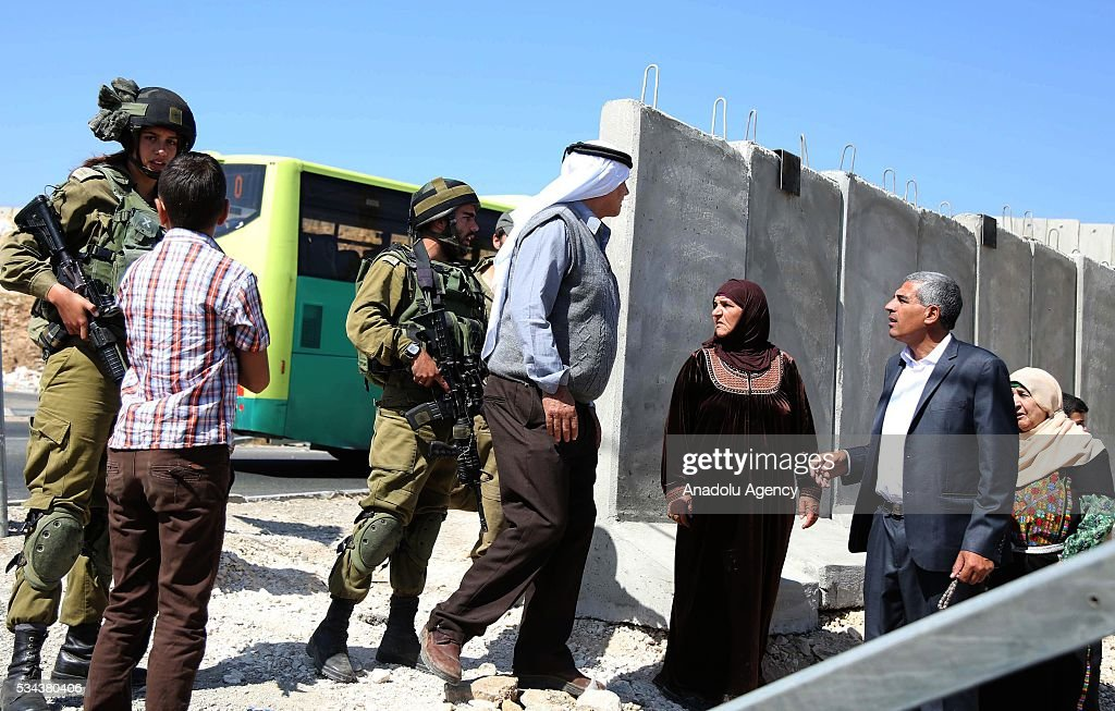 Israeli security guards talk with Palestinians as Israeli security forces increase the security measures around Hizma district of Jerusalem on May 26, 2016.