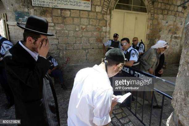 Israeli security look on as Ultra Orthodox Jews pray at one of the entrances of the alAqsa mosque compound during the Jewish Tisha 'Av commemoration...