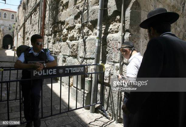 Israeli security look on as Ultra Orthodox Jews pray at one of the entrances of the alAqsa mosque compound the third holiest place in Islam during...
