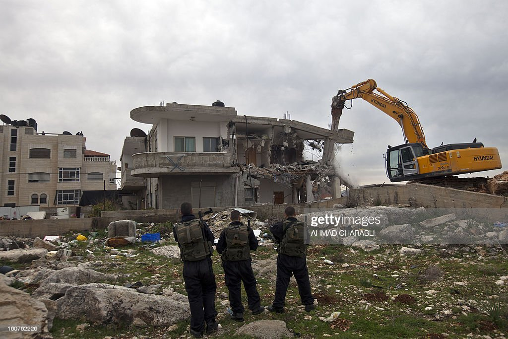 Israeli security officers keep watch as a bulldozer destroys a Palestinian house in the Arab east Jerusalem neighborhood of Beit Hanina on February 5, 2013. Palestinian homes built without a construction permit are often demolished by order of the Jerusalem municipality. AFP PHOTO/AHMAD GHARABLI