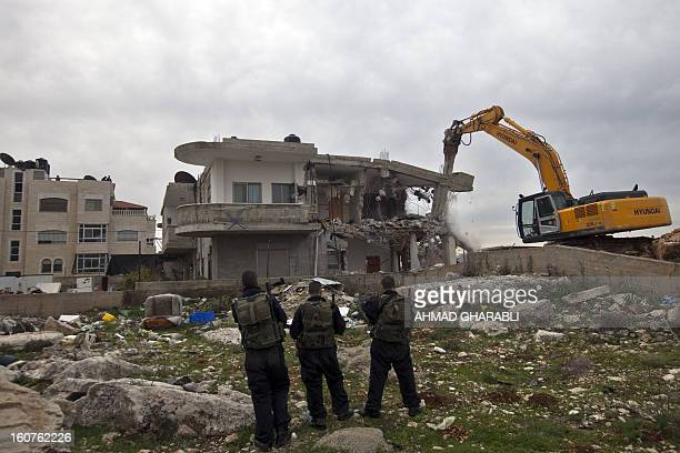 Israeli security officers keep watch as a bulldozer destroys a Palestinian house in the Arab east Jerusalem neighborhood of Beit Hanina on February 5...