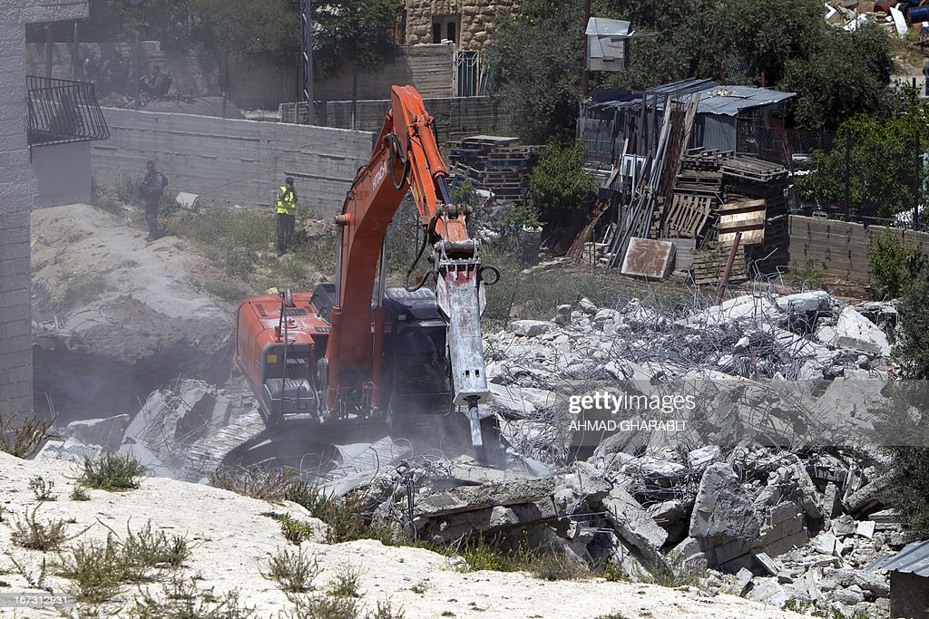 Israeli security officers stand guard as a bulldozer hired by the Jerusalem municipality destroys a Palestinian house in the Israeli annexed East Jerusalem neighbourhood of al-Tur on April 24, 2013. Palestinian homes built without a construction permit are often demolished by order of the Jerusalem municipality. AFP PHOTO/AHMAD GHARABLI