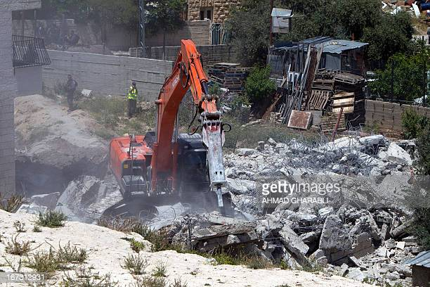 Israeli security officers stand guard as a bulldozer hired by the Jerusalem municipality destroys a Palestinian house in the Israeli annexed East...