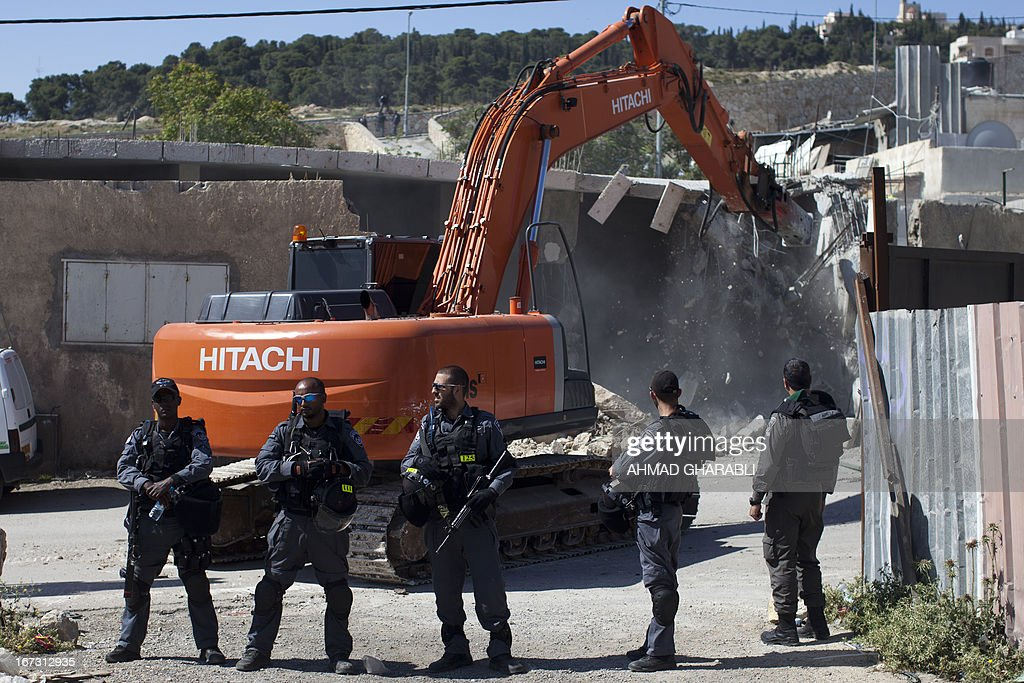 Israeli security officers stand guard as a bulldozer hired by the Jerusalem municipality destroys a Palestinian house in the Israeli annexed East Jerusalem neighborhood of al-Tur on April 24, 2013. Palestinian homes built without a construction permit are often demolished by order of the Jerusalem municipality.