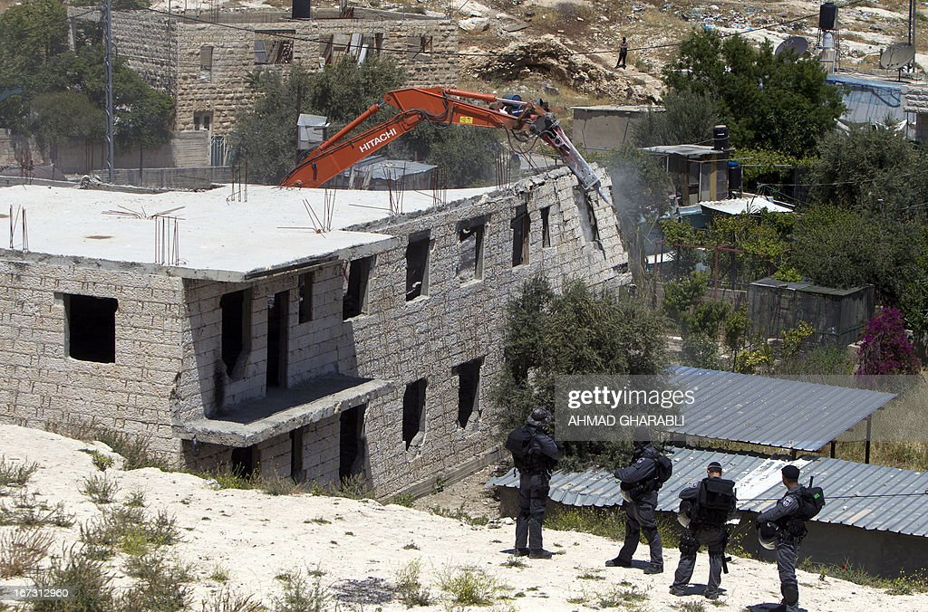 Israeli security officers stand guard as a bulldozer hired by the Jerusalem municipality destroys a Palestinian house in the Israeli annexed East Jerusalem neighbourhood of al-Tur on April 24, 2013. Palestinian homes built without a construction permit are often demolished by order of the Jerusalem municipality.