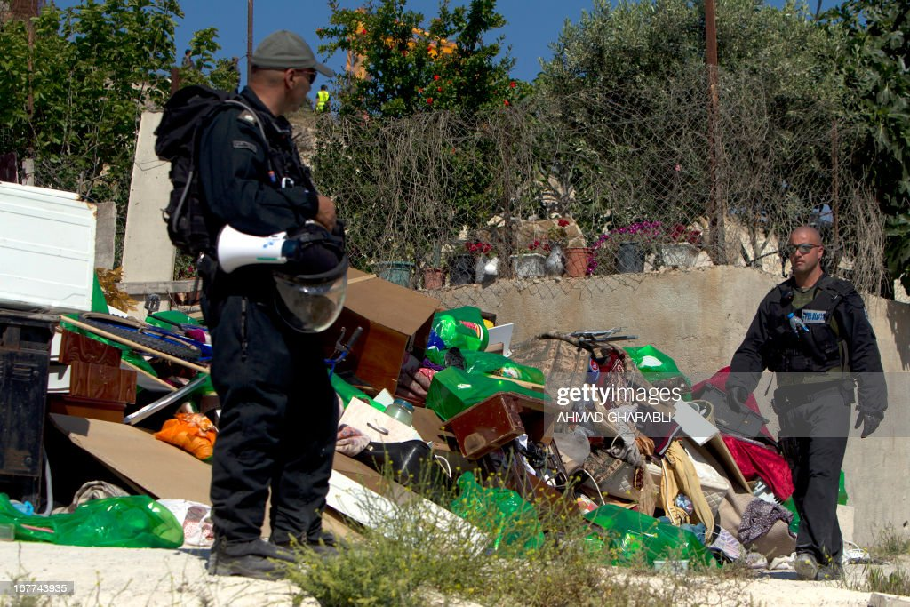 Israeli security officers stand guard as a bulldozer hired by the Jerusalem municipality destroys a Palestinian house in the Israeli annexed East Jerusalem neighborhood of al-Tur on April 29, 2013. Palestinian homes built without a construction permit are often demolished by order of the Jerusalem municipality.