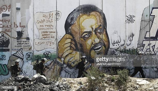 Israeli security officers walk next to a mural depicting jailed Fatah leader Marwan Barghuti at the Israeli Qalandiya checkpoint between Jerusalem...