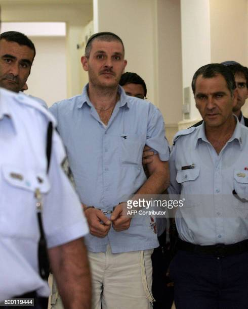 Israeli settler Asher Weissgan is escorted by policemen at the Jerusalem District Court 27 September 2006 The Jerusalem District Court sentenced the...