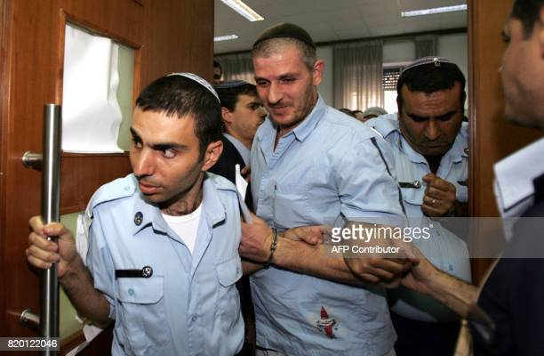Israeli settler Asher Weissgan is escorted by policemen out of the courtroom at the Jerusalem District Court 27 September 2006 The Jerusalem District...