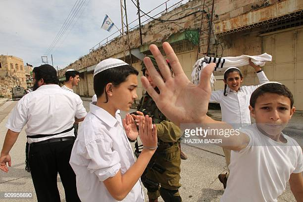 Israeli settler youth gesture to the camera in an attempt to block the view as security forces gather at the site where a Palestinian woman tried to...
