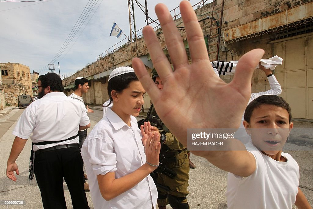 Israeli settler youth gesture to the camera in an attempt to block the view as security forces gather at the site where a Palestinian woman tried to stab an Israeli soldier before being shot dead, in the Israeli occupied West Bank city of Hebron, on February 13, 2016. An Israeli army statement said that 'An assailant drew a knife and attempted to stab a soldier,', 'Responding to the attack, forces fired at the perpetrator, resulting in her death.' The Palestinian health ministry confirmed that a woman was killed but could not immediately give her age or name. The army statement said that the incident occurred near Hebron's shared religious site known to Jews as the Cave of the Patriarchs and to Muslims as the Ibrahimi Mosque, a site of frequent friction between the sides. BADER