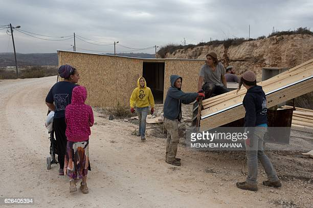 Israeli settler youths build a new wooden structure in the settlement outpost of Amona which was established in 1997 in the Israelioccupied West Bank...