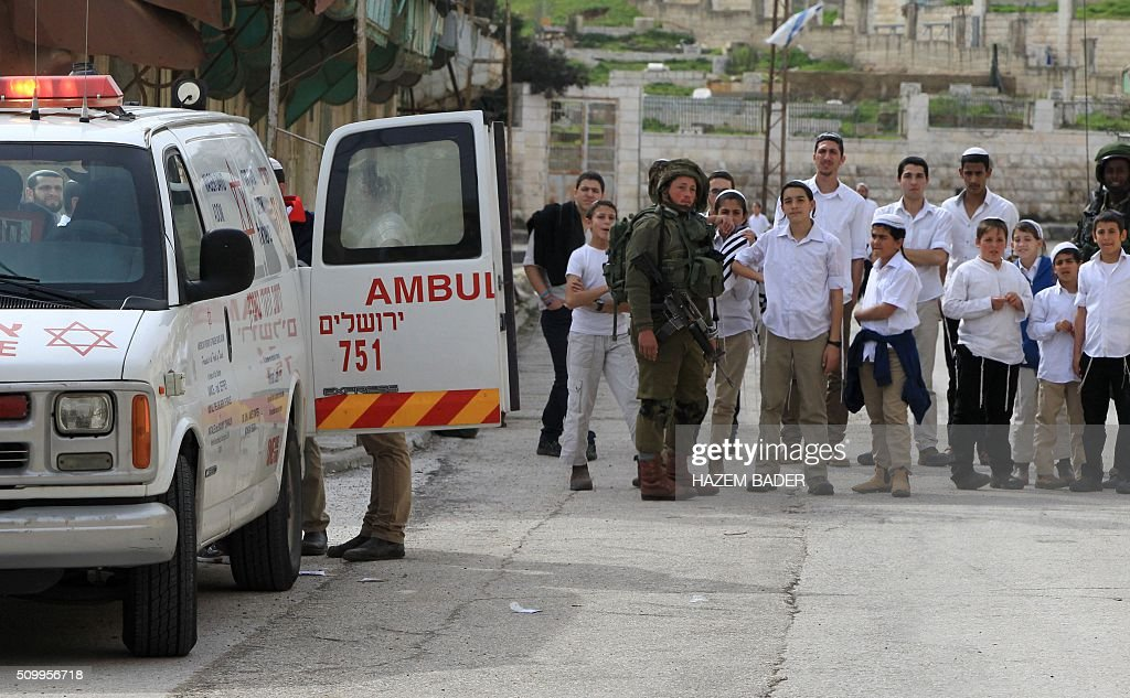 Israeli settlers and security forces gather at the site where a Palestinian woman tried to stab an Israeli soldier before being shot dead, in the Israeli occupied West Bank city of Hebron, on February 13, 2016. An Israeli army statement said that 'An assailant drew a knife and attempted to stab a soldier,', 'Responding to the attack, forces fired at the perpetrator, resulting in her death.' The Palestinian health ministry confirmed that a woman was killed but could not immediately give her age or name. The army statement said that the incident occurred near Hebron's shared religious site known to Jews as the Cave of the Patriarchs and to Muslims as the Ibrahimi Mosque, a site of frequent friction between the sides. BADER