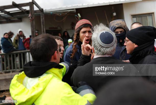 TOPSHOT Israeli settlers argue with officials as Israeli security forces gather at the Amona outpost northeast of Ramallah on February 1 2017 to...