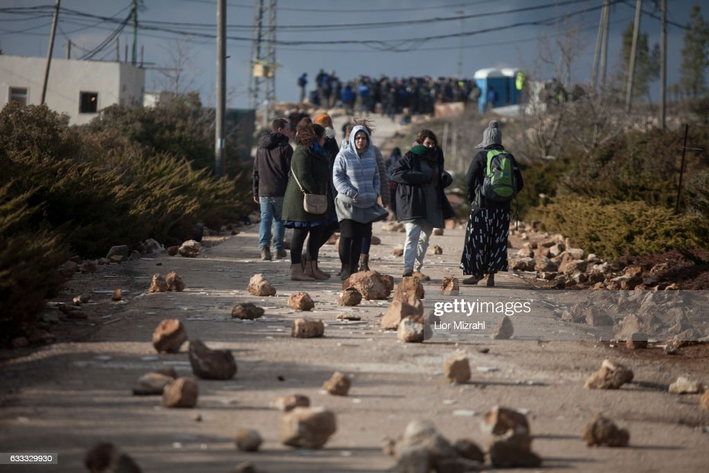 Israeli settlers block the road with stones ahead of the upcoming eviction of the illegal Jewish settlement on February 1, 2017 in Amona, West Bank. Israeli Security forces have started evacuating residents from the illegal outpost of Amona in the West Bank on Wednesday, after hundreds of youths streamed into the outpost to fight the evacuation.