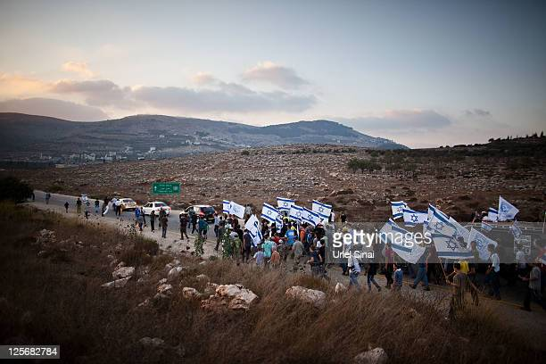 Israeli settlers carry Israeli flags as they participate in a protest march against Palestinian statehood September 20 2011 from the West Bank Jewish...