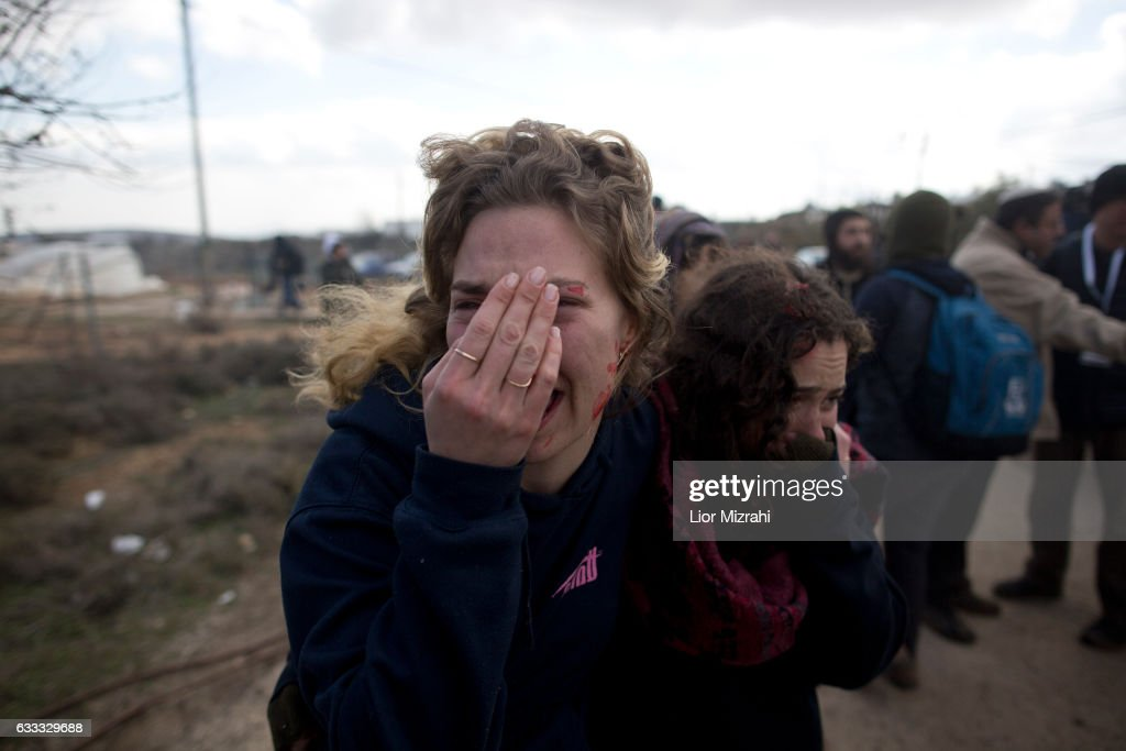 Israeli settlers cover their face as Israeli security forces arrive to the illegal Jewish settlement on February 1, 2017 in Amona, West Bank. Israeli Security forces have started evacuating residents from the illegal outpost of Amona in the West Bank on Wednesday, after hundreds of youths streamed into the outpost to fight the evacuation.