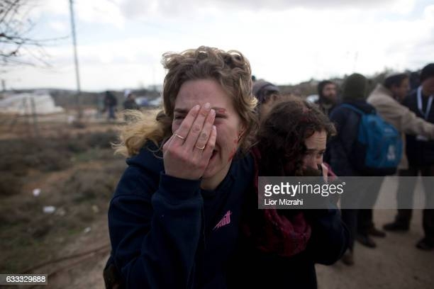 Israeli settlers cover their face as Israeli security forces arrive to the illegal Jewish settlement on February 1 2017 in Amona West Bank Israeli...