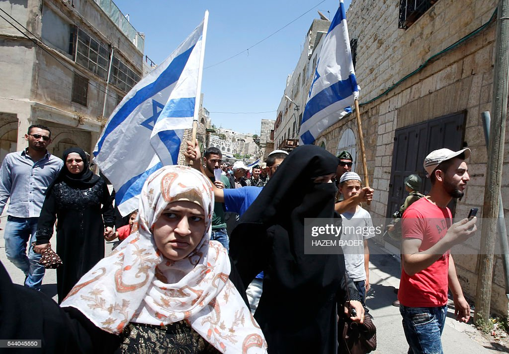 Israeli settlers (back) guarded by soldiers and border police march in a street in the Israeli occupied West Bank city of Hebron as Palestinian Muslims (front) head back from the Friday prayers at the Ibrahimi mosque, or the Tomb of the Patriarch, a religious site to both Muslims and Jews, on July 1, 2016. A Palestinian woman attempted to stab an Israeli guard at a flashpoint West Bank shrine and was shot dead, Israeli police said, the third violent incident in two days. / AFP / HAZEM