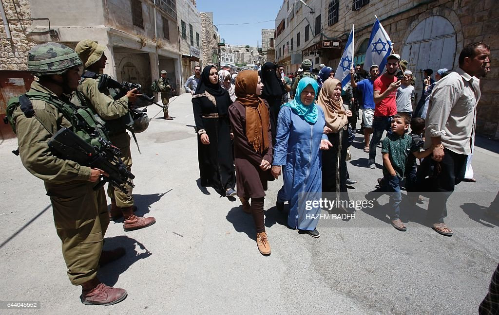 Israeli settlers (R-back) guarded by soldiers and border police march in a street in the Israeli occupied West Bank city of Hebron as Palestinian Muslims (C) head back from the Friday prayers at the Ibrahimi mosque, or the Tomb of the Patriarch, a religious site to both Muslims and Jews, on July 1, 2016. A Palestinian woman attempted to stab an Israeli guard at a flashpoint West Bank shrine and was shot dead, Israeli police said, the third violent incident in two days. / AFP / HAZEM