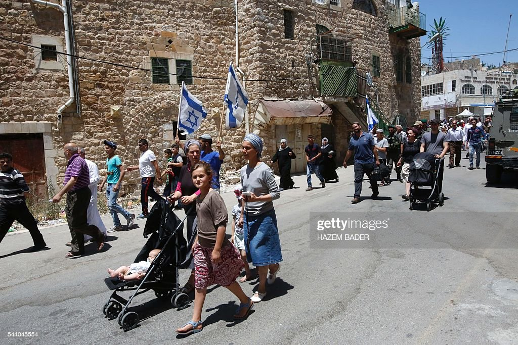 Israeli settlers (C-front) guarded by soldiers and border police march in a street in the Israeli occupied West Bank city of Hebron as Palestinian Muslims (back) head back from the Friday prayers at the Ibrahimi mosque, or the Tomb of the Patriarch, a religious site to both Muslims and Jews, on July 1, 2016. A Palestinian woman attempted to stab an Israeli guard at a flashpoint West Bank shrine and was shot dead, Israeli police said, the third violent incident in two days. / AFP / HAZEM